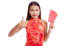 La muchacha asiática en vestido chino del cheongsam manosea con los dedos para arriba con rojo envuelve Fotos de archivo libres de regalías