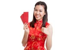 La muchacha asiática en vestido chino del cheongsam manosea con los dedos para arriba con rojo envuelve Fotografía de archivo
