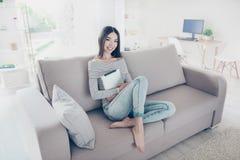 La muchacha asiática encantadora joven está sosteniendo su tableta, sentándose en bei Imágenes de archivo libres de regalías