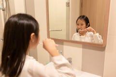 La muchacha asiática está cepillando sus dientes y está sonriendo mientras que mira en th foto de archivo libre de regalías