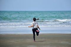 La muchacha asiática está corriendo en la playa en el mar Imagenes de archivo