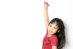 La muchacha asiática está escribiendo en un fondo blanco Imagen de archivo
