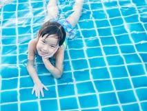 La muchacha asiática está jugando en la piscina Foto de archivo libre de regalías
