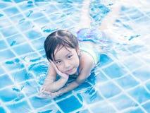 La muchacha asiática está jugando en la piscina Fotos de archivo