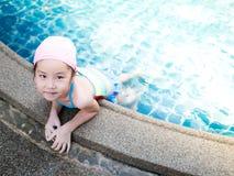 La muchacha asiática está jugando en la piscina Imagen de archivo libre de regalías