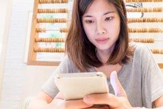 La muchacha asiática está mandando un SMS alguien en su teléfono Fotografía de archivo