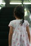 La muchacha asiática está subiendo con la escalera móvil Fotos de archivo