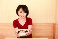 la muchacha asiática está tomando un cuenco de ensalada de los pescados Foto de archivo libre de regalías
