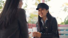 La muchacha asiática feliz está hablando con su amigo femenino en café de la calle después que tuesta y que tintinea los vidrios  almacen de video