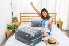 La muchacha asiática feliz linda joven acabó de embalar el equipaje de la maleta en cama en el dormitorio, listo para ir al extra imagen de archivo libre de regalías