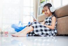 La muchacha asiática feliz que usa el auricular para escucha música por smartphone mientras que en el cuarto vivo Imagen de archivo libre de regalías