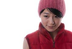 La muchacha asiática hermosa con el casquillo rojo Foto de archivo