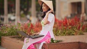 La muchacha asiática hermosa habla en un ordenador portátil en la calle y un vestido nacional hermoso Ao Dai almacen de metraje de vídeo