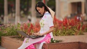 La muchacha asiática hermosa habla en un ordenador portátil en la calle y un vestido nacional hermoso Ao Dai con un casquillo en  almacen de video