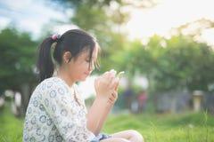 La muchacha asiática hermosa que usa el teléfono elegante con la sensación se relaja Fotos de archivo libres de regalías