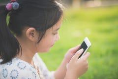 La muchacha asiática hermosa que usa el teléfono elegante con la sensación se relaja Imagen de archivo