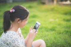 La muchacha asiática hermosa que usa el teléfono elegante con la sensación se relaja Fotografía de archivo