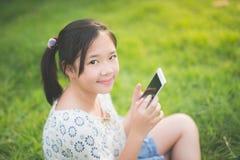 La muchacha asiática hermosa que usa el teléfono elegante con la sensación se relaja Foto de archivo libre de regalías