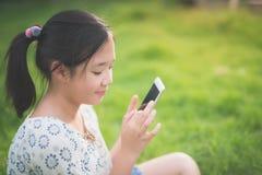 La muchacha asiática hermosa que usa el teléfono elegante con la sensación se relaja Imagen de archivo libre de regalías