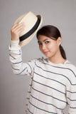 La muchacha asiática hermosa saca un sombrero Imágenes de archivo libres de regalías