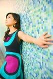 La muchacha asiática hermosa se inclina detrás en la pared azul Fotos de archivo