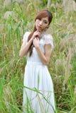 La muchacha asiática hermosa se vistió en un vestido blanco que jugaba en la hierba foto de archivo libre de regalías
