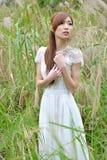 La muchacha asiática hermosa se vistió en un vestido blanco que jugaba en la hierba imágenes de archivo libres de regalías