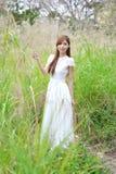 La muchacha asiática hermosa se vistió en un vestido blanco que jugaba en la hierba fotografía de archivo libre de regalías