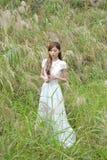 La muchacha asiática hermosa se vistió en un vestido blanco que jugaba en la hierba imagen de archivo