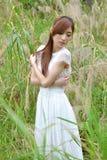 La muchacha asiática hermosa se vistió en un vestido blanco que jugaba en la hierba fotos de archivo libres de regalías