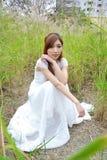 La muchacha asiática hermosa se vistió en un vestido blanco que jugaba en la hierba foto de archivo