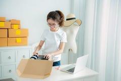 La muchacha asiática joven es freelancer con su asunto privado en casa imagen de archivo libre de regalías