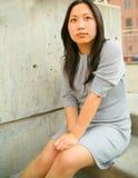 La muchacha asiática joven pensativa sienta al aire libre Foto de archivo libre de regalías
