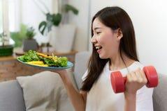 La muchacha asiática joven que lleva a cabo la ensalada y la pesa de gimnasia roja se está sentando en el sofá con la cara de la  fotografía de archivo