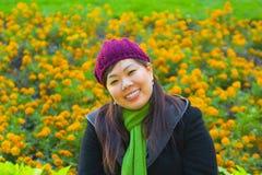 La muchacha asiática joven se sienta en las flores imagen de archivo libre de regalías