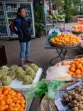 La muchacha asiática joven vende la fruta en una calle de la ciudad fotografía de archivo libre de regalías