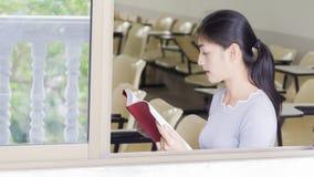La muchacha asiática lee un libro rojo Fotos de archivo