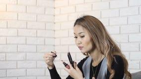 La muchacha asiática linda pinta sus labios, maquillaje 50 fps almacen de metraje de vídeo