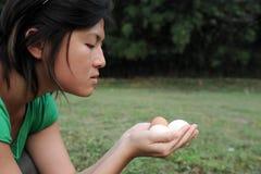 La muchacha asiática mira los huevos imagenes de archivo