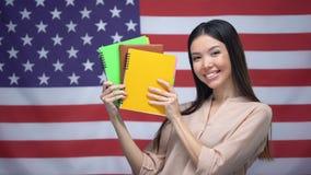 La muchacha asiática que sonríe contra los E.E.U.U. señala el fondo por medio de una bandera, estudiante que sostiene cuadernos almacen de metraje de vídeo