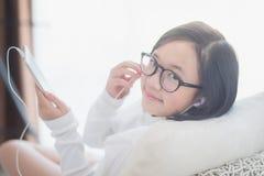 La muchacha asiática que usa el auricular para escucha música Foto de archivo