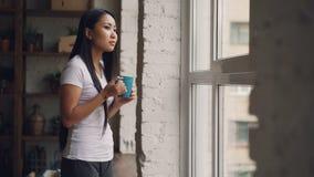 La muchacha asiática relajada va a la ventana con la taza de café, está pareciendo exterior y está bebiendo después la sonrisa y  almacen de video