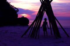 La muchacha asiática se coloca debajo de una bóveda de bambú en la playa foto de archivo