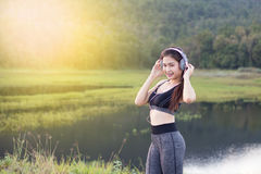 La muchacha asiática se divierte los vestidos que escucha la música por los auriculares fotos de archivo libres de regalías