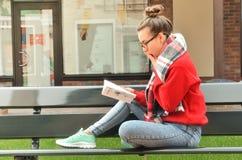 La muchacha asiática se sienta en un banco y lee un libro Imagenes de archivo