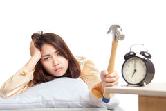 La muchacha asiática soñolienta despierta el despertador del golpe con el martillo imagen de archivo