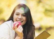 La muchacha asiática sonríe feliz, relajándose el días de fiesta con las manzanas en h imagen de archivo