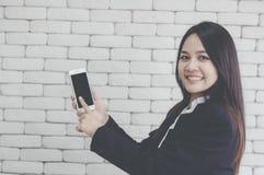 La muchacha asiática sonríe y utiliza su mano para señalar smartphone, la pared de ladrillo blanca del fondo, conceptos comercial imagenes de archivo