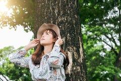 La muchacha asiática sonriente de los jóvenes se relaja debajo de árbol grande en el parque en HOL imagen de archivo libre de regalías
