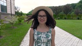 La muchacha asiática sonriente en el sombrero y el vestido del verano camina a lo largo de la pista en el parque disfruta de vida almacen de metraje de vídeo